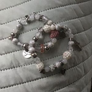 Bracelets are white, pink, silver, with charms.